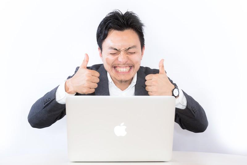パソコンの前で喜ぶ人の画像