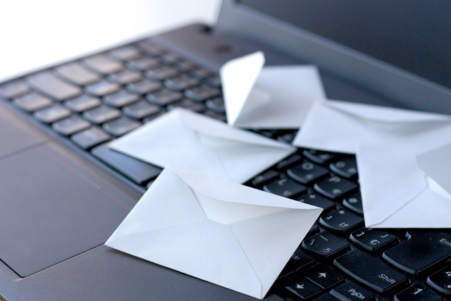 パソコンの上に手紙が散らばっている画像