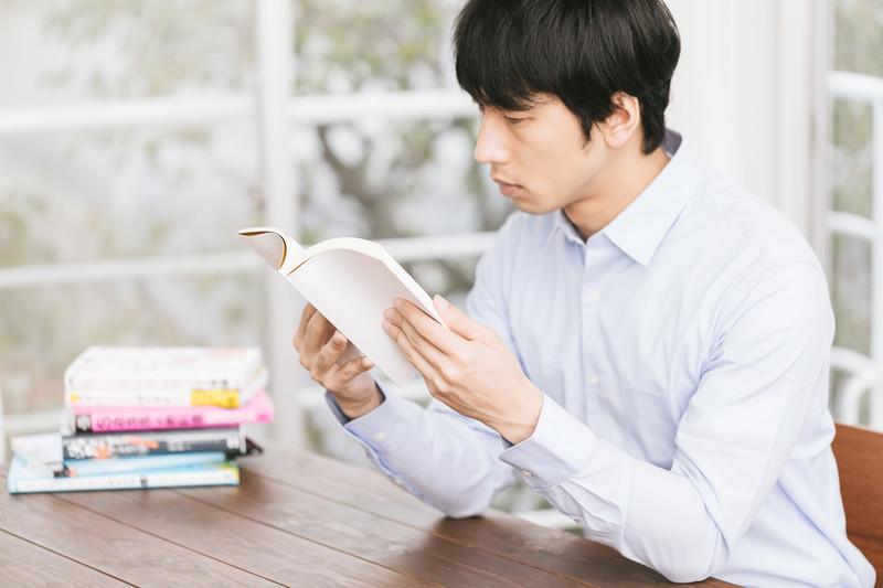 本を読んで勉強する男性の画像